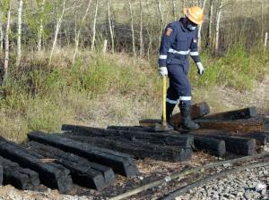 Firefighter Putting Out Fire on Burning Rail Ties